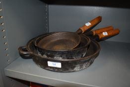 A selection of wooden handled cast iron skillet frying or sauce pans