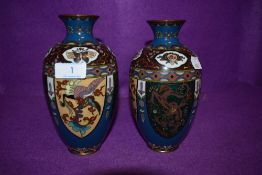 A pair of cloisonné vases depicting mythological beasts, flowers and more.