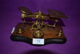 A set of brass apothecary scales on wooden mount with some weights.