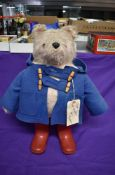 A Gabrielle Designs plush covered Padding Bear soft toy, wearing blue jacket and red wellingtons,