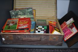 A vintage travel case containing a collection of vintage games and jigsaws including Monopoly,