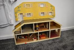A 1970's style wooden two storey Dolls House having a small selection of wooden and plastic