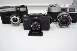 Three cameras, a Ricoh FF-1, a Konica S2, and a Russian OMO Cosmic Symbol