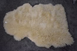 A pale colour sheep skin rug or throw