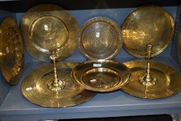 A pair of well cast brass candle sticks having knopped stems and a selection of various brass plates