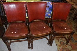 A set of six early 20th Century oak frame dining chairs having red leather seats and backs