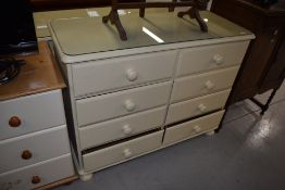 A cream bedroom chest of four by four drawers, width approx. 110cm
