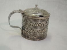 A George II silver mustard pot of drum form having moulded band decoration with blue glass liner and