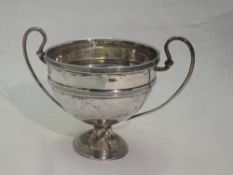 A small Edwardian silver trophy bowl of traditional form having loop handles and reeded