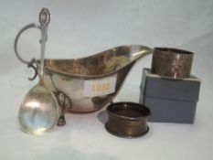 An Edwardian silver sauce boat of plain form having trefoil paw feet, loop handle and reeded rim,