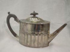A Georgian silver teapot of drum form having gadrooned decoration and fruitwood handle, bearing