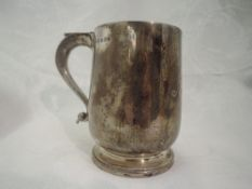 An Edwardian silver tankard of plain baluster form on circular pedestal foot with thumb rest loop