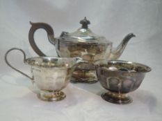 A silver three piece matched tea set of circular form having facetted decoration, fruitwood handle