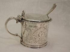 A Victorian silver mustard pot of drum form having engraved decoration, hinged lid and blue glass