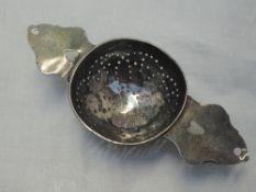 A Queen Anne Britannia silver lemon strainer having pierced bowl and heart cuts to the handles,