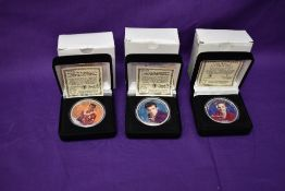Three Morgan Mint Elvis Presley 2004 Silver Dollars in cases, each coloured on one side, each named,