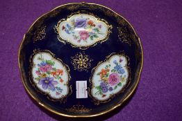 An antique pin dish having cobolt blue gold and hand decorated floral scenes bearing crossed