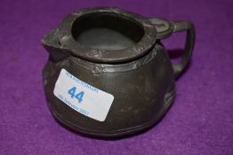 A small antique pewter jug stamped Tudric to base possibly Liberties and co having age related