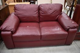 A modern burgundy leatherette two seater settee, width approx. 160cm