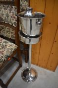 A chrome ice bucket on stand and cocktail shaker