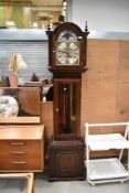 A reproduction long case clock having glazed panel to front
