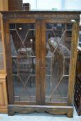 An early 20th Century oak astral glazed bookcase having blind fretwork frieze, width approx. 98cm,