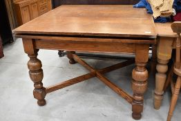 An early to mid 20th Century oak drawer leaf table on cross stretcher and bulbous column legs,