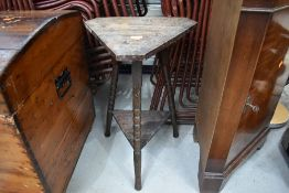 A late 19th/early 20th Century carved tricorn style plant stand/side table on triple turned legs,