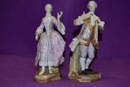 A pair of Meissen figurines of gentleman and companion, the gent is wearing a pink frock coat with