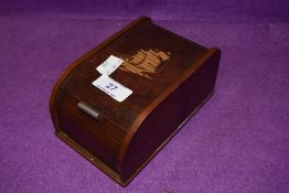 A vintage wooden roll top cigarette box with kinetic internal movement, having ship design to top.
