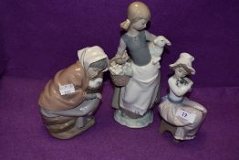 A Lladro figurine, Girl with Lamb 4835 and two Nao figurines, Girl with Duck in Basket and Girl with