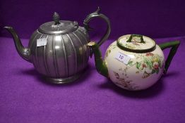 Two teapots, one pewter having intricate design the other having Doulton Burslem cream ground with