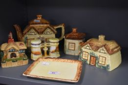 A collection of hand painted country cottage ceramics including tea pot, cheese dome, lidded sugar