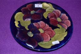 A Vintage Moorcroft plate having dark blue ground and anemone or clematis pattern.