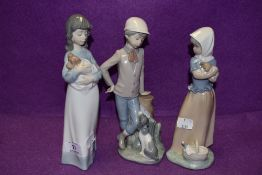 Three Lladro Nao figurines, two girls with puppies and a boy with dog at his feet.