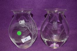 A pair of glass vases having etched designs one with butterfly design the other tree and landscape