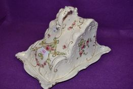 An antique cheese dish having hand tinted swags and roses pattern with gilt detailing.