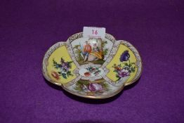 A porcelain pin dish or saucer bearing a Dresden style mark to base