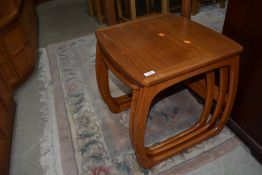 A vintage teak Nathan nest of three tables, of stylised form
