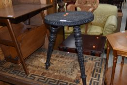 A traditional carved tri legged stool, with Islamic influences