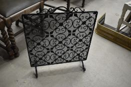 A wrought iron and wirework fire guard/screen