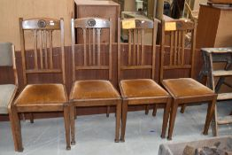 A set of four early 20th century golden oak dining chairs having rail backs, later dralon