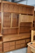 A vintage teak Nathan wall unit, having glazed display and lockable cocktail section, over triple
