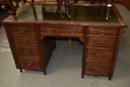 A late Victorian mahogany desk in the Aesthetic style, later skiver leather top and mounted on