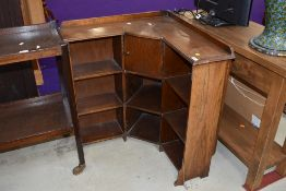 An early 20th Century oak corner bookshelf of small proportions, having integral smokers cabinet,