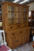A top quality modern solid golden oak dresser, having open shelves flanked by displays over three