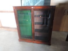 A mahogany and glazed free standing upright Gun Case, spaces for 7 guns and four shelves width
