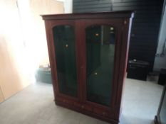 A mahogany and glazed free standing upright Gun Cabinet, spaces for 9 guns and three drawers