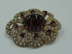 A yellow metal brooch having central garnet cabouchon within an open surround of seed pearls and