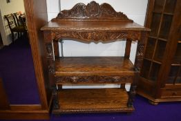 A traditional oak buffet sideboard having frieze drawers to undershelf with carved 'Greenman'